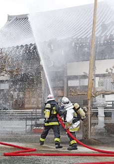 本堂の屋根に放水する消防隊員
