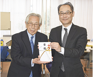 寄付金を手にする小川理事長(左)と河原支店長