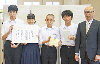 賞状などを手にする生徒。右は鈴木校長