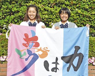 スローガンが書かれた旗を手にする鈴木さん(左)と秋本さん