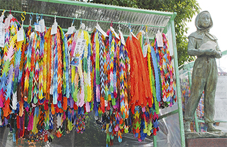ガラスのうさぎ像の隣に飾られた色とりどりの千羽鶴