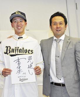 オリックスの由田慎太郎スカウト(右)に帽子とユニフォームを着せてもらい、サインを披露する本田投手