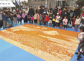 完成したみかんモザイクアートを囲む参加者たち