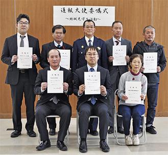 「通報大使」の委嘱を受けた事業者の代表者と松嶋署長(後列中央)=7日・大磯警察署講堂