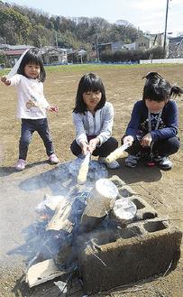 焚き火料理を体験する子ども