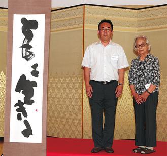 櫻井さん(右)から現地の校長へ作品が手渡された(世界芸術文化交流会提供)