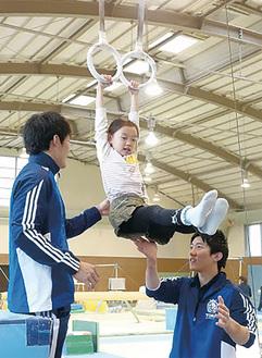 学生のサポートで吊り輪を体験する小学生(ラビッツクラブ湘南二宮提供)