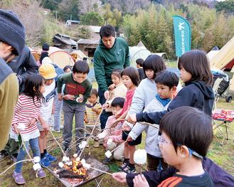 焚き火でマシュマロを焼く子どもたち