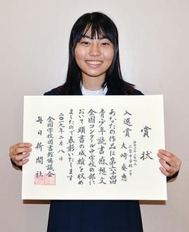 青少年読書感想文全国コンクール入選賞の賞状を手にする大崎さん