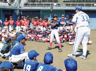 講師の市川さんからバッティングの上達法を学ぶ小学生