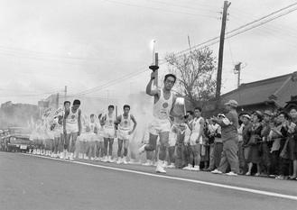 1964年に大磯を走る聖火ランナー(大磯町郷土資料館提供)