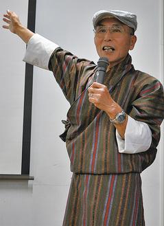 ブータンの民俗衣装を着て講演する坪田さん