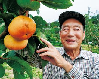 ずっしりと実った大玉柿と生産者の鈴木さん