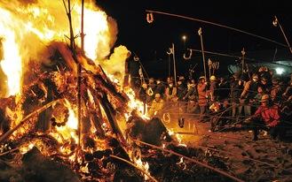 燃え盛る炎に団子を括り付けた竹竿を伸ばす参加者(昨年)