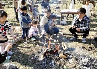 焚き火で団子を焼く親子