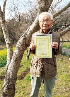 2004年に植えた木の前で認定証を手にする齋藤さん