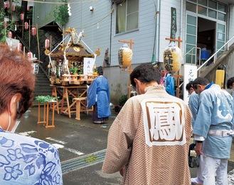 神輿を前に安寧を祈願する祭礼の参列者