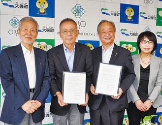 協定書に署名した重田会長(中央左)と坂巻代表取締役(中央右)