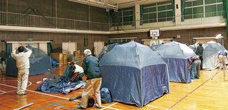 感染症対策で体育館にテントを設営する参加者(中井町提供)
