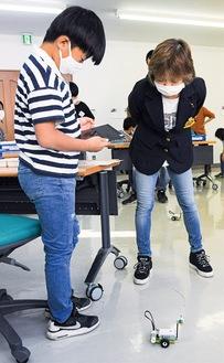 ロボットの動きを確かめる小学生