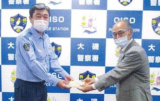 日原署長(左)へステッカーを手渡す杉崎会長(大磯警察署提供)