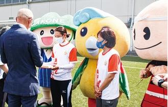 箱根町長(左)から特産品を受け取るカルマ選手