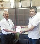 目録を手渡す鈴木伸幸さん(右)
