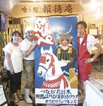 「報徳庵」で看板を囲む北村さん、高橋さん、押田一秀さん(左から)
