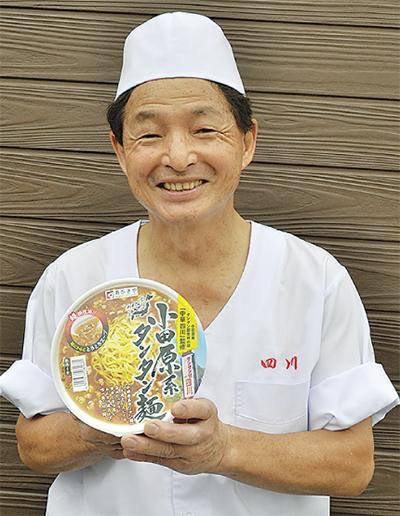 カップ麺を手に笑顔の内田さん
