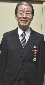 勲章を胸に笑顔の豊嶋氏