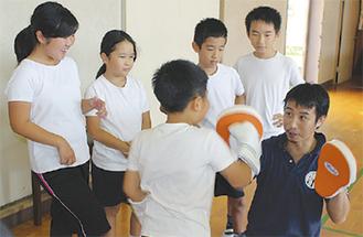 松田さんの構えるミットめがけパンチを打ち込む児童たち