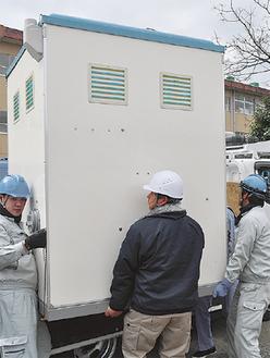 仮設トイレを設置する参加者=城北中学校