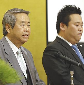 壇上で社長交代を伝える民雄氏(左)と息子の弘樹氏