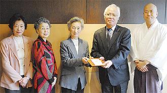 毎日新聞社の澤晴夫支局長(右から2番目)に手渡された