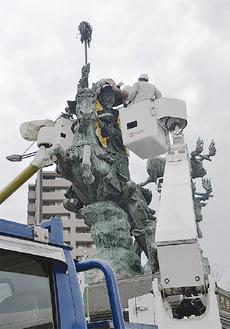 クレーン車2台を使い早雲公に陣羽織を着せる=4月21日・小田原駅西口