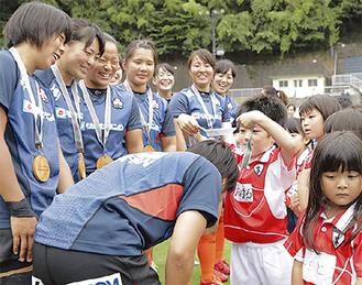 木製のメダルを女子日本代表候補の首に掛ける小田原ラグビースクールの選手