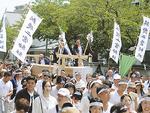 大勢の市民に引かれて神社へ運ばれる鳥居の御用材