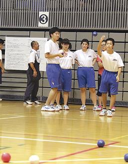 目標の白球に向かってボールを投げる生徒。チームメイトは球の行方を真剣な眼差しで見守った