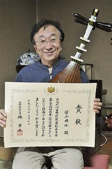 祖父の琵琶と賞状を手に笑顔の笹本さん