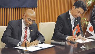 協定書にサインするラティーフ副会長と加藤市長