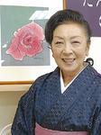 花びらの染料で描いた作品の前に立つ磯村さん