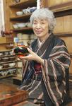 23歳の時に出会った行作さんが作った椀を手にする野田とし子さん。工房にて