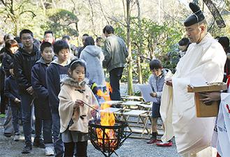 火の中に感謝を込めて筆を入れる参拝者たち