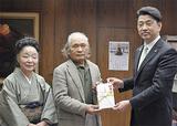 寄付金を手渡す鈴木三郎さん(中央)