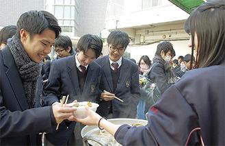 在校生(右)から丁寧に手渡される一杯