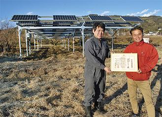 賞状を手にする川久保さん(右)と小山田さん。後ろは太陽光発電パネルを設置した畑=市内曽我岸