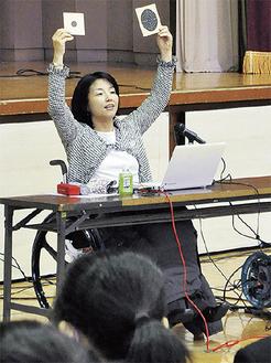 講演する田口さん。手に持っているのは射撃の的