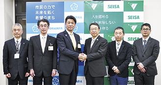加藤市長と握手を交わす井上理事長(右から3番目)