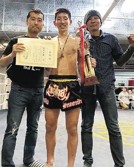 優勝を喜ぶ鈴木君(中央)、飯山真代表(左)、ムエタイトレーナーのナンプーさん(右)(谷山ジム提供)
