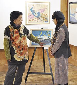 作品の説明をする須藤さん(左)